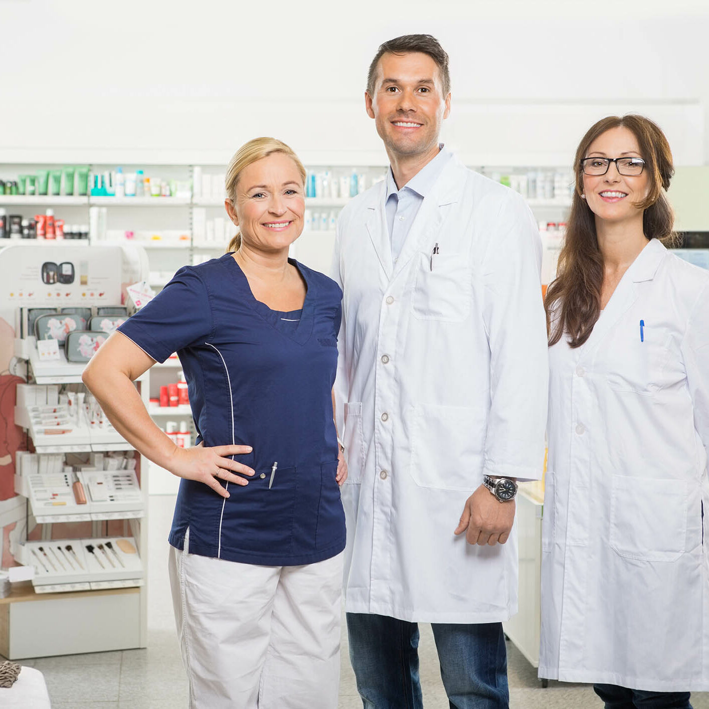 Portrait of confident female assistant with pharmacists standing in pharmacy
